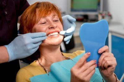 New Dentures Patient Smiling In The Mirror